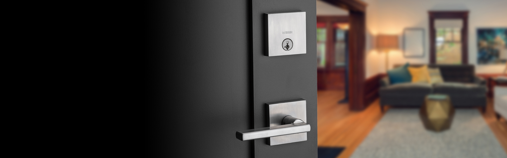 Downtown deadbolt featuring SmartKey in satin nickel with Halifax lever in satin nickel leading into a living room