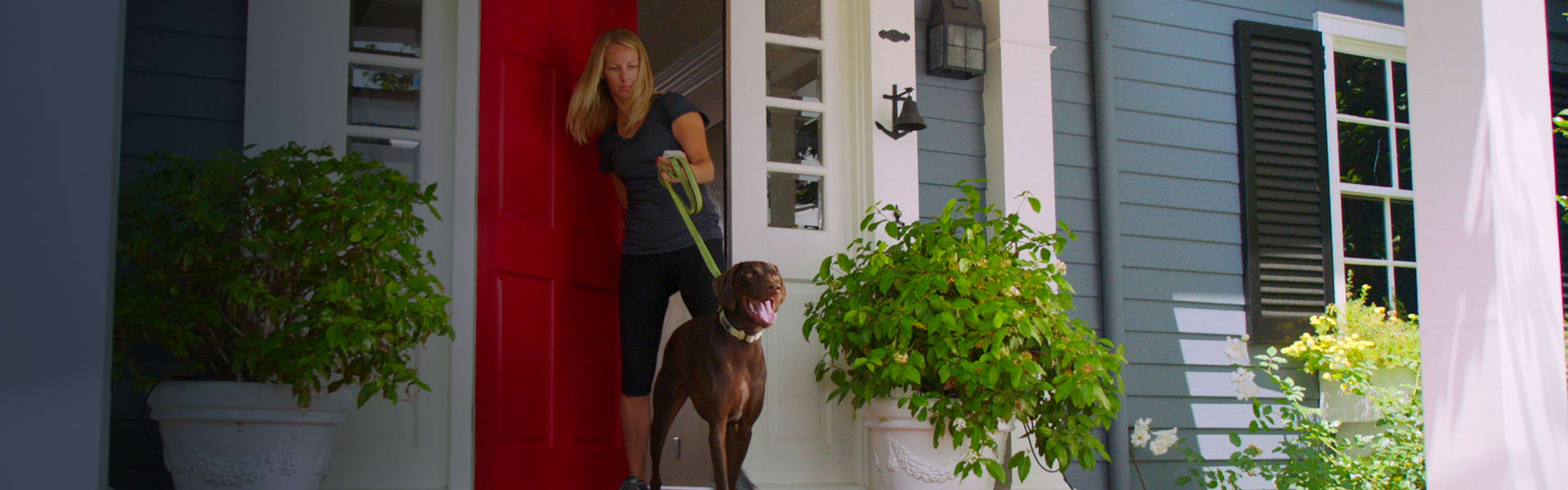 Women exiting her front door with her dog on a leash