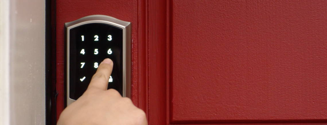 Finger touching a Smart Code 10 touchscreen lock on a red door