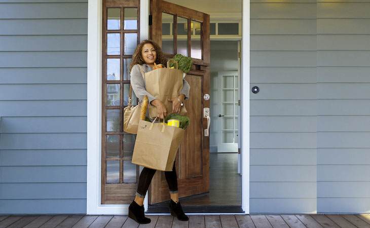 Woman carrying groceries walking into a house smiling