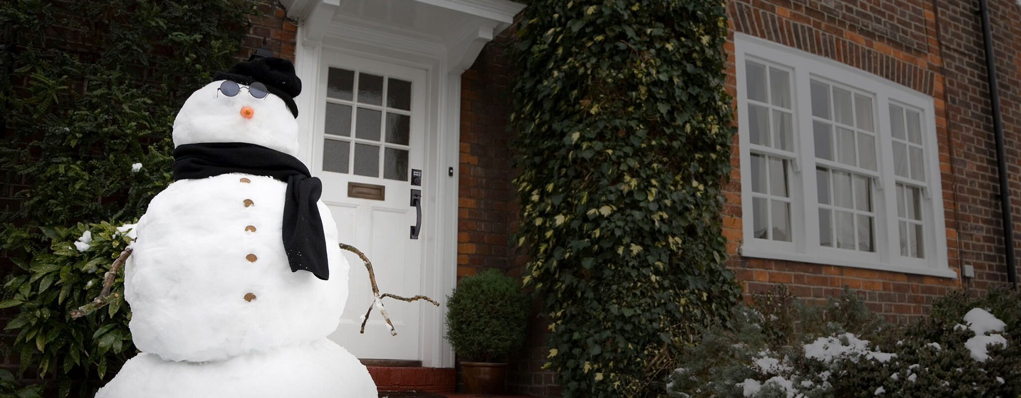 Large snowman with glasses, scarf and hat sitting on front lawn outside of a house