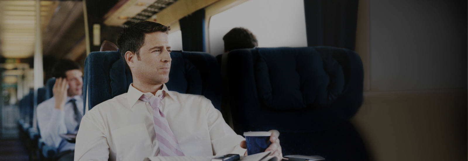 Man on train gazes out window while holding a cup of coffee